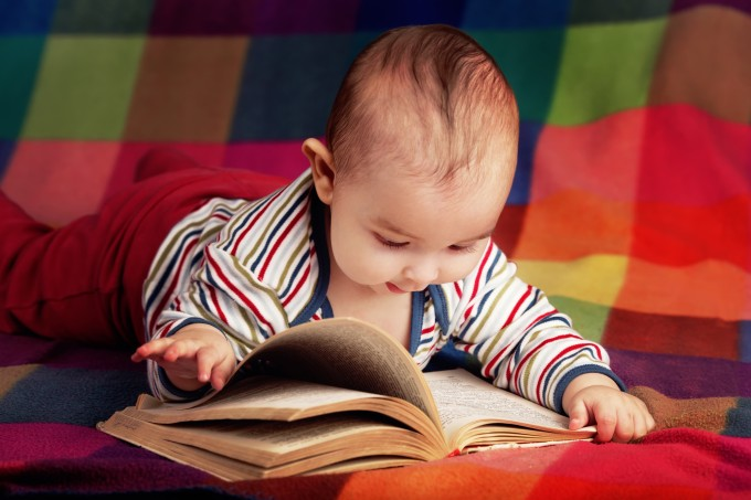 cute baby reading book on colorful background