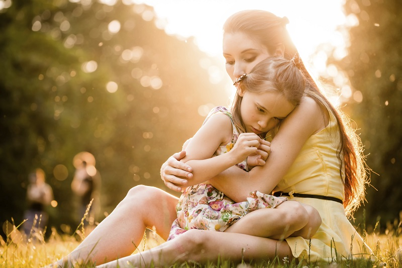 Mother is cuddling her worried child outdoor in nature
